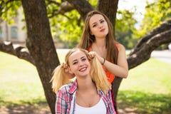 Los amigos que se divierten, escuchando la música y se relajan en parque Los adolescentes felices pasan tiempo en la ciudad Foto de archivo libre de regalías