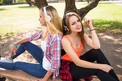 Los amigos que se divierten, escuchando la música y se relajan en parque Los adolescentes felices pasan tiempo en la ciudad Imágenes de archivo libres de regalías