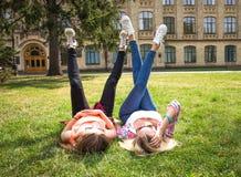 Los amigos que se divierten, escuchando la música y se relajan en parque Los adolescentes felices pasan tiempo en la ciudad Fotos de archivo