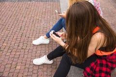 Los amigos que se divierten, escuchando la música y se relajan en parque Los adolescentes felices pasan tiempo en la ciudad Imagen de archivo libre de regalías