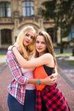Los amigos que se divierten, escuchando la música y se relajan en parque Los adolescentes felices pasan tiempo en la ciudad Fotografía de archivo libre de regalías