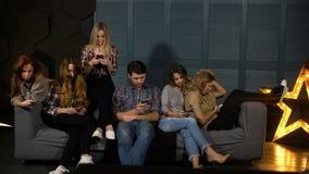 Los amigos que se sientan en el sofá y el reloj llaman por teléfono almacen de video