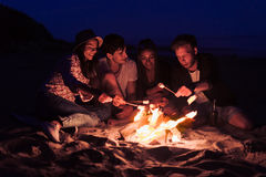 Los amigos que se sientan en la playa tintinean los vidrios cerca de hoguera fotografía de archivo