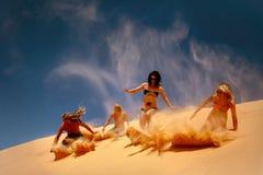 Los amigos resbalan abajo la duna de arena amarilla Imagenes de archivo