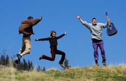 Los amigos saltan sobre un campo de hierba en la montaña Foto de archivo libre de regalías