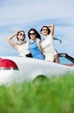 Los amigos se colocan en el auto con las manos para arriba Imagen de archivo libre de regalías