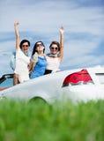 Los amigos se colocan en el cabriolé con las manos para arriba Imagenes de archivo