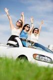 Los amigos se colocan en el coche blanco con las manos para arriba Fotos de archivo libres de regalías