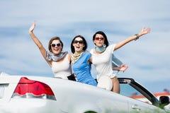 Los amigos se colocan en el coche con las manos para arriba Fotografía de archivo