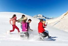 Los amigos se divierten en el invierno en nieve fresca foto de archivo libre de regalías