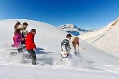 Los amigos se divierten en el invierno en nieve fresca imagenes de archivo
