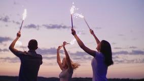 Los amigos se divierten en fuegos artificiales Con después de la puesta del sol, un partido de la playa vídeo de la cámara lenta