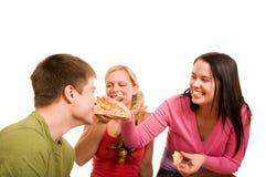Los amigos se están divirtiendo y están comiendo la pizza Foto de archivo libre de regalías
