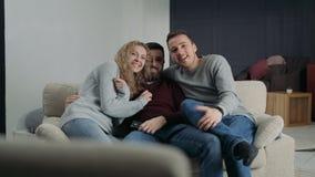Los amigos se están sentando en el sofá en casa metrajes