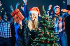 Los amigos se ríen en la Navidad holyday con el árbol de navidad Foto de archivo libre de regalías