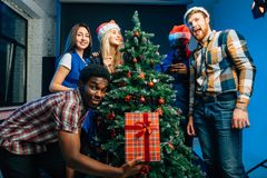 Los amigos se ríen en la Navidad holyday con el árbol de navidad Imágenes de archivo libres de regalías