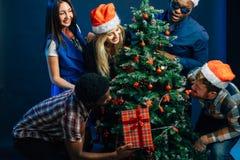 Los amigos se ríen en la Navidad holyday con el árbol de navidad Fotografía de archivo libre de regalías