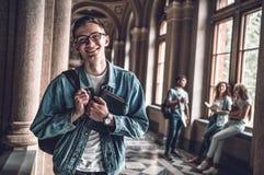 Los amigos se ríen la universidad Retrato de un estudiante masculino joven hermoso con sus amigos en el fondo imagenes de archivo