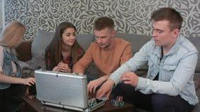 Los amigos se sientan en un sofá y juegan al juego imagen de archivo libre de regalías
