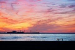 Los amigos siluetean caminar en la playa en la puesta del sol Foto de archivo