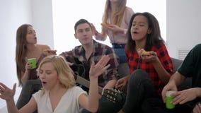 Los amigos sonrientes comen la pizza y cantan canciones con la guitarra que se sienta en el sofá en el partido casero metrajes