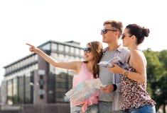 Los amigos sonrientes con el mapa y la ciudad dirigen al aire libre Imagen de archivo