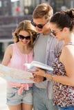 Los amigos sonrientes con el mapa y la ciudad dirigen al aire libre Fotografía de archivo