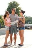Los amigos sonrientes con el mapa y la ciudad dirigen al aire libre Fotos de archivo libres de regalías