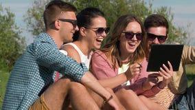 Los amigos sonrientes con PC de la tableta en el verano parquean metrajes