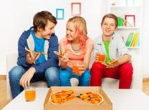 Los amigos sonrientes felices comen junta la pizza en casa Fotografía de archivo libre de regalías