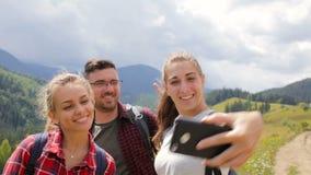 Los amigos toman imágenes juntas por la tarde en las montañas metrajes