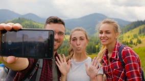 Los amigos toman imágenes juntas por la tarde en las montañas almacen de metraje de vídeo