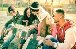 Los amigos urbanos del estilo agrupan tener tiempo de la diversión hacia fuera en el parque del patín Imágenes de archivo libres de regalías