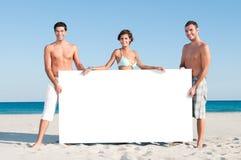 Los amigos visualizan el cartel blanco Imagen de archivo libre de regalías