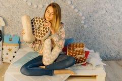 Los amortiguadores con las letras de amor son sostenidos por el adolescente joven mientras que se sientan en el sofá Foto de archivo libre de regalías