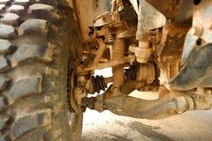 Los amortiguadores de choque y la zapata de freno en el tren de aterrizaje del coche de Bigfoot es mancha del suelo fangoso Imágenes de archivo libres de regalías