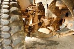 Los amortiguadores de choque y la zapata de freno en el tren de aterrizaje del coche de Bigfoot es mancha del suelo fangoso Foto de archivo libre de regalías