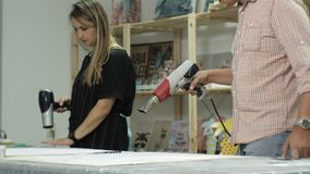 Los amos en el estudio del arte procesan el árbol con un secador de pelo de la construcción, alcanzan el efecto del envejecimient almacen de metraje de vídeo