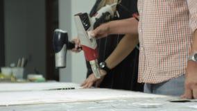 Los amos en el estudio del arte procesan el árbol con un secador de pelo de la construcción, alcanzan el efecto del envejecimient metrajes
