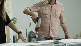 Los amos en el estudio del arte procesan el árbol con un secador de pelo de la construcción, alcanzan el efecto del envejecimient almacen de video