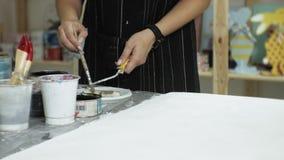 Los amos en el estudio del arte procesan la madera con la pintura y la masilla, alcanza el efecto del envejecimiento almacen de metraje de vídeo