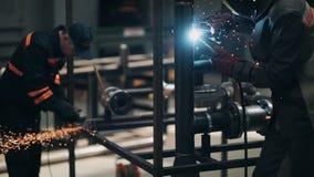 Los amos en el taller realizan el corte y la soldadura del metal almacen de metraje de vídeo