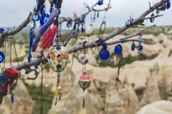 Los amuletos y las decoraciones turcos tradicionales cuelgan en las ramas de un árbol de los deseos contra el contexto del paisaj imagenes de archivo