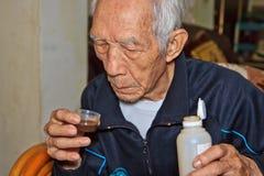 Los ancianos para beber el jarabe de la tos Imagen de archivo