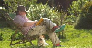Los ancianos retiraron al hombre que se relajaba al aire libre leyendo un libro que disfrutaban del retiro almacen de video