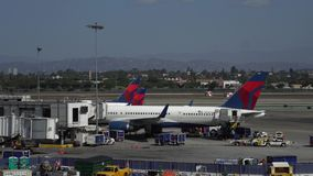 Los Angeles, CA United States - 10 02 2019: Delta airplanes unloading and loading near the terminal at LAX, Los Angeles. Los Angeles, CA / United States - 10 02 stock video