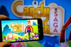 Los Angeles, Californië, de V.S. - 21 Februari 2019: Handen die een smartphone met CANDY CRUSH SAGA-spel houden tegen het grote s royalty-vrije stock fotografie