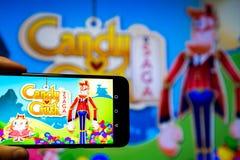 Los Angeles, Californië, de V.S. - 21 Februari 2019: Handen die een smartphone met CANDY CRUSH SAGA-spel houden tegen het grote s stock afbeeldingen