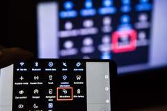 Los Angeles, Californië, de V.S. - 21 Februari, 2019 Handen die een smartphone op de achtergrond van het scherm houden MirrorShar royalty-vrije stock foto's