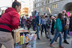 2nd Annual Women`s March - Hotdog vendor and marchers. LOS ANGELES, CALIFORNIA - JANUARY 20, 2018:  2nd Annual Women`s March marchers passing by a street food Stock Photography